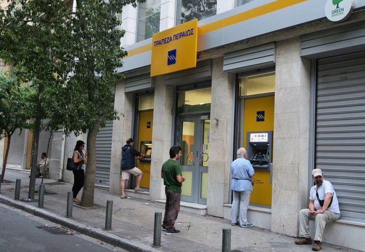 La situación generada por la crisis en Grecia es perceptible en cualquier calle de Atenas en donde se ven a numerosos clientes en las sucursales y los cajeros automáticos. (Notimex)