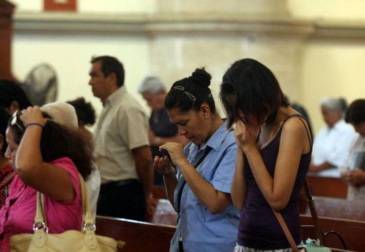 La Iglesia invita a hacer oración por los enfermos de sida. Imagen de un grupo de fieles orando en una iglesia católica. (Milenio Novedades)