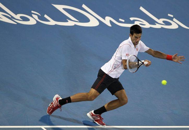 El serbio Novak Djokovic devuelve una pelota al francés Jo-Wilfried Tsonga en la semifinal del torneo de exhibición de Abu Dabi. (Agencias)