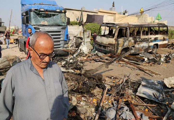 Civiles observan el sitio donde hizo explosión un auto bomba en el barrio Mshtal, en el este de Bagdad, Irak, el 17 de noviembre de 2014. (AP/Karim Kadim)