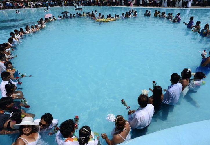 Más de un centenar de parejas participa en una boda masiva en una piscina pública. (EFE)