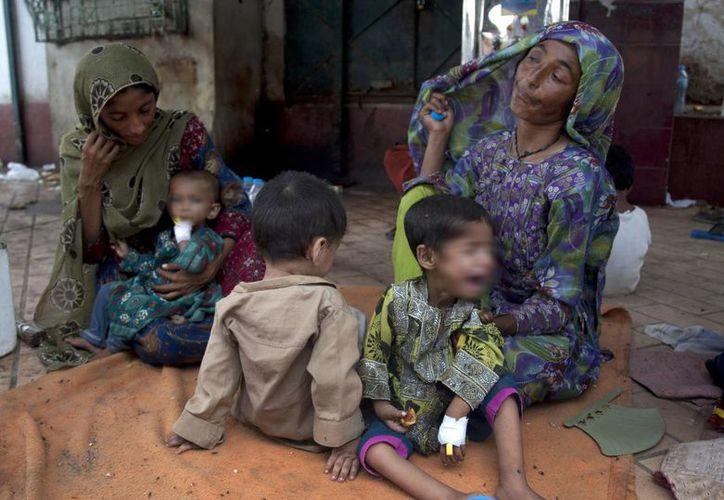 Niños paquistaníes que sufren de deshidratación debido a las condiciones meteorológicas extremas son atendidos por sus madres mientras esperan su turno en un hospital local en Karachi, Pakistán. (Agencias)