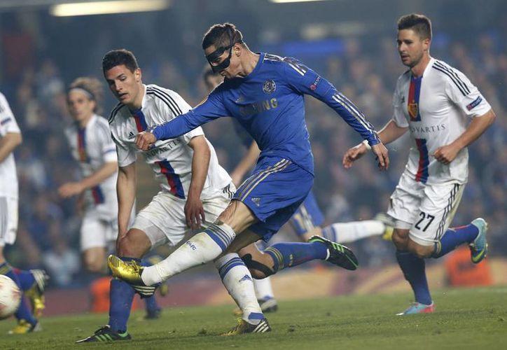 El delantero español del Chelsea, Fernando Torres (centro), realiza un disparo de gol frente a jugadores del Basilea durante el partido de vuelta de la semifinal de la Liga Europa en el estadio Stamford Bridge. (Agencias)