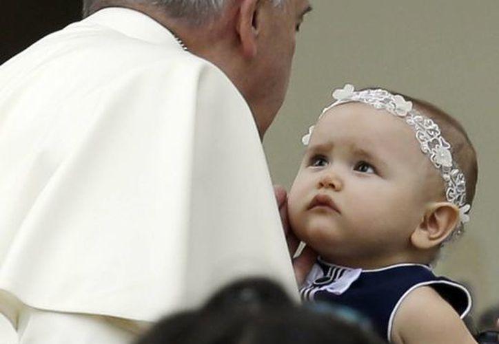 El Papa Francisco acaricia a una niña al llegar a la Plaza de San Pedro para su audiencia semanal, el miércoles 15 de octubre de 2014. (Foto: AP)