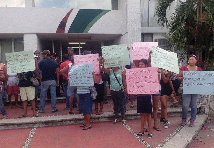 Los manifestantes gritan consignas y llevan pancartas en el Palacio de Gobierno. (Sergio Orozco/SIPSE)