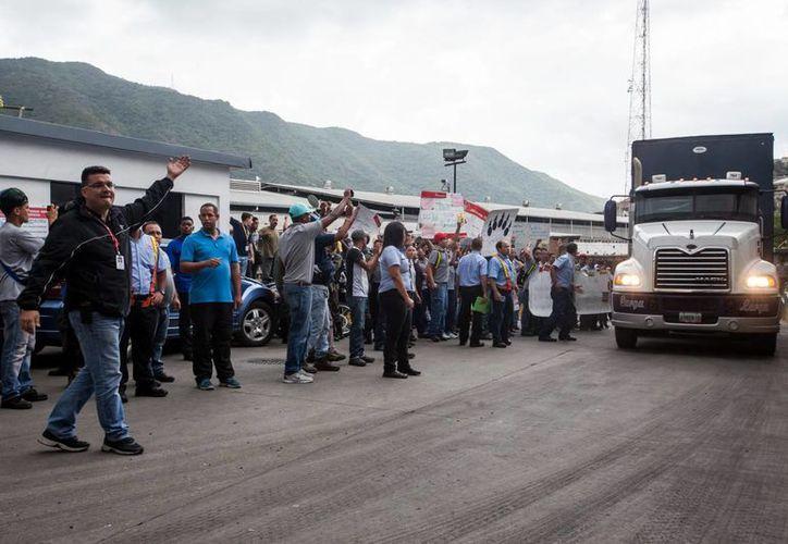 Trabajadores de la embotelladora de Pepsi Cola y de Empresas Polar protestan afuera de una planta de la embotelladora de Pepsi Cola ubicada al oeste de Caracas, que tiene a partir de este jueves 60 días para desalojar. (EFE)
