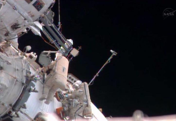 Imagen del video provisto por la NASA de los cosmonautas rusos Pavel Vinogradov (izq) y Roman Romanenko durante la caminata espacial. (Agencias)