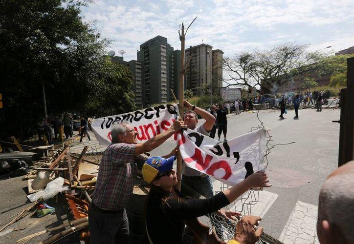 Manifestantes arman una barricada en el barrio La Boyera en Caracas, Venezuela. (Agencias)