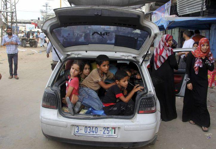 Familias palestinas que perdieron sus casas a causa de los bombardeos en la Franja de Gaza huyen hacia el campo de refugiados de Khan Younis en el sur de Gaza. (Foto AP)