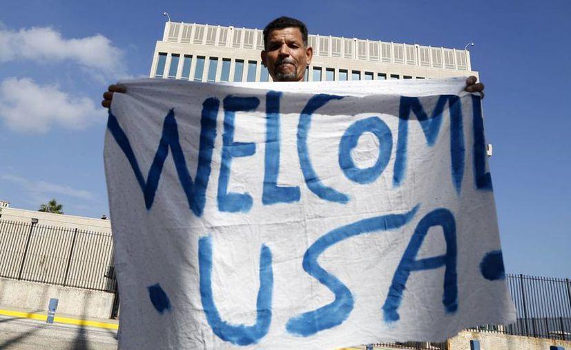 En agosto próximo reabrirá sus puertas la embajada de Estados Unidos en Cuba. En la imagen, un cubano muestra un cartel con el texto 'Bienvenido EU' frente a la que serán las instalaciones diplomáticas en La Habana. (AP)
