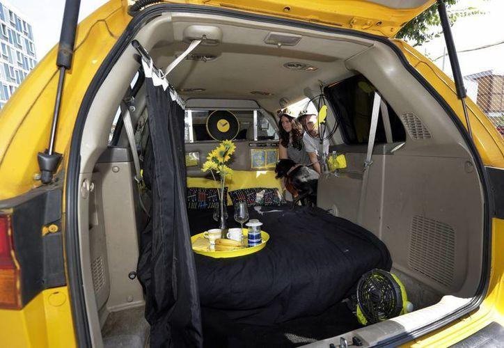 Los huéspedes de Airbnb Michael y Tabitha Akins, acompañados de su perro Bagheera, asomándose a una minivan taxi Honda Odyssey 2002, modificada para ser usada como alojamiento en Queens, Nueva York. (Agencias)