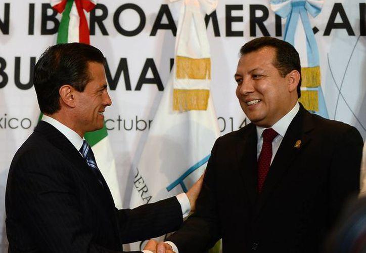 El presidente de la Comisión Nacional de Derechos Humanos, Raúl Plascencia, quien en la foto aparece junto al presidente Enrique Peña, consideró que 'hemos hecho el trabajo que nos corresponde hasta el límite de las capacidades'. (Foto de archivo de Notimex)