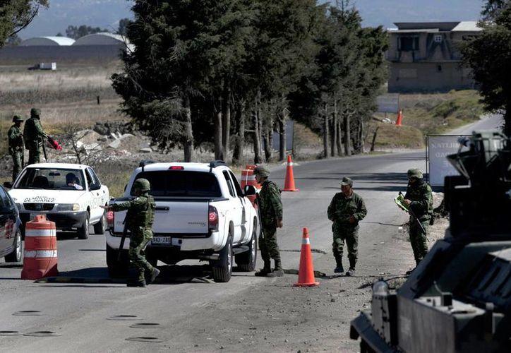 Fotografía de un puesto de control de militares cerca de la prisión de máxima seguridad del Altiplano en Almoloya, donde Joaquín 'El Chapo' Guzmán  se encuentra detenido después de su recaptura. El jefe del cártel de Sinaloa niega haber enviado droga a EU. (Foto AP / Marco Ugarte)