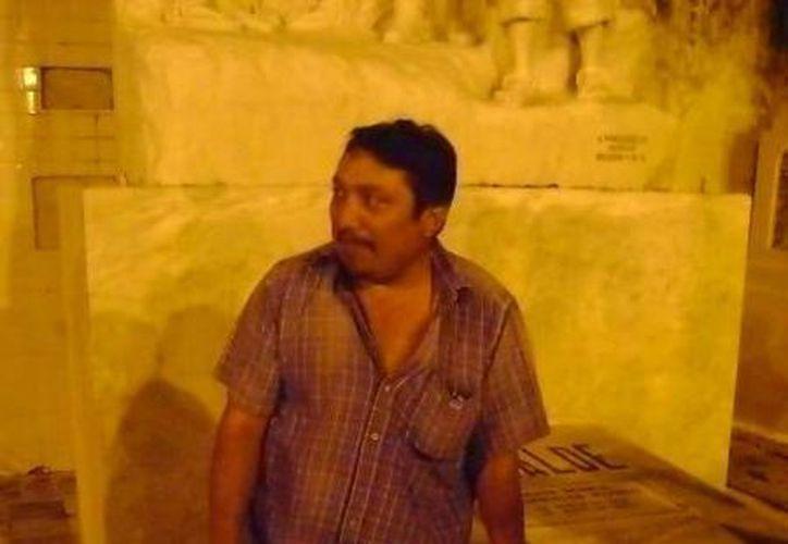 El velador del panteón don Santiago Loría, junto a la tumba en donde vio al señor de blanco. (Jorge Moreno/SIPSE)
