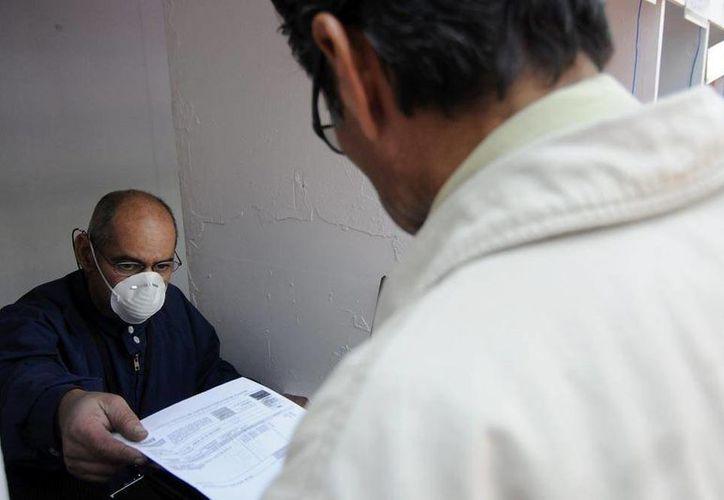 La influenza ha cobrado la vida de 445 persona en México, dos de ellas en Yucatán. La foto corresponde al Ayuntamiento de Tijuana, donde los empleados usan cubrebocas como medida de prevención. (Archivo/NTX)