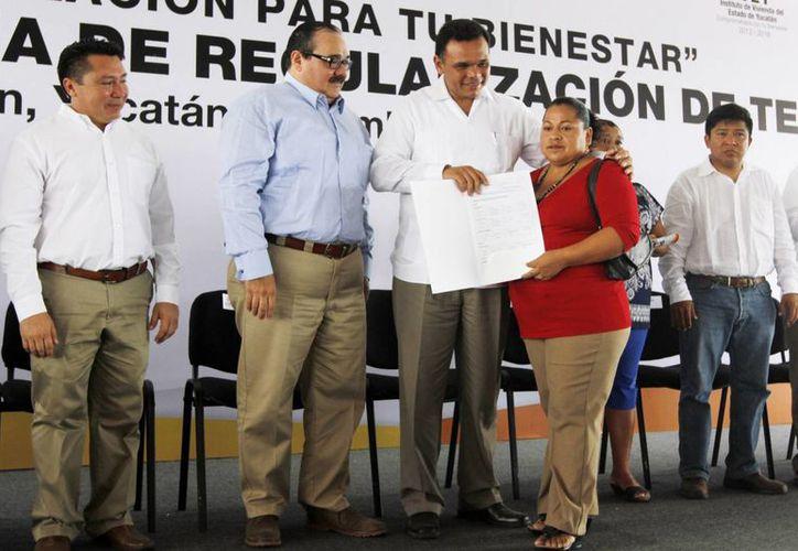 Ramírez Marín (camisa azul) acompañó al gobernador de Yucatán, Rolando Zapata (c), a la entrega de títulos de propiedad del programa Regulariza por tu bienestar, en Kanasín. (Cortesía)