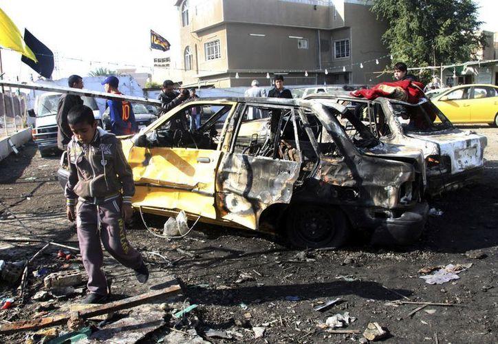 Iraquíes inspeccionan el escenario de un ataque con coche bomba en el distrito de Al Hurriya, en Bagdad, Irak. (EFE/Archivo)