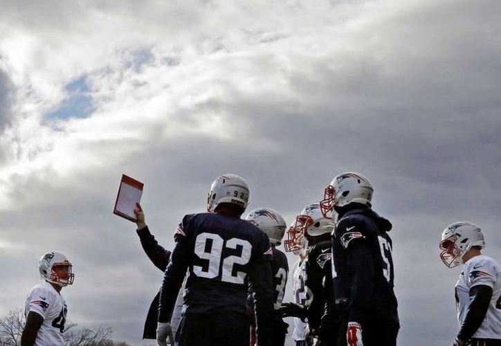 Los jugadores de los Patriots de Nueva Inglaterra consultan el libro de jugadas durante una práctica realizada el miércoles 28 de diciembre de 2016. (AP)
