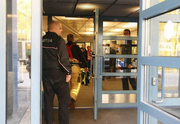 Un guardia de seguridad y trabajadores de emergencia entran en la escuela donde se realizó el ataque. (Agencias)