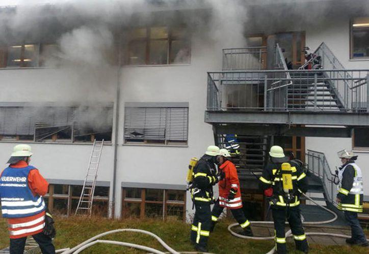 Bomberos tratan de apagar las llamas en el taller de madera en Titisee-Neustadt. (Agencias)