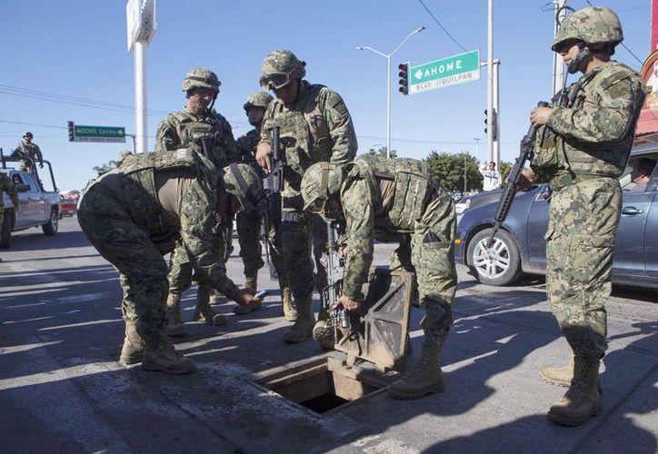 Infantes de marina mexicanos inspeccionan un pozo de registro donde se encontraron armas de alto poder que dejó El Chapo durante su huída en Los Mochis, Sinaloa. (Foto AP / Christian Palma)