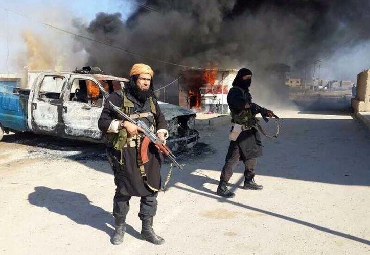 Shakir Waheib, a la izquierda, miembro de alto rango del Estado Islámico de Irak y el Levante, grupo vincualdo con Al Qaeda, permanece cerca de un vehículo policial incendiado en la provincia de Anbar, en Irak. (Agencias)