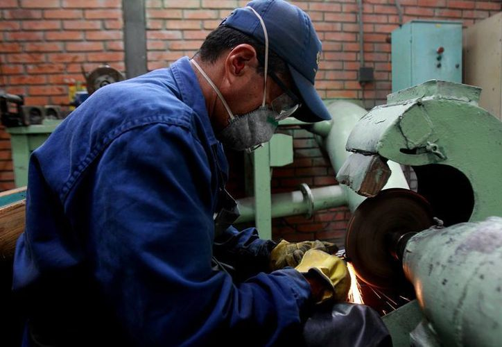 """Fotografía de un hombre trabajando en la planta """"José María Córdova"""" de la Industria Militar (Indumil), situada en el municipio de Soacha (Colombia), donde se produce la pistola Córdova. (EFE)"""