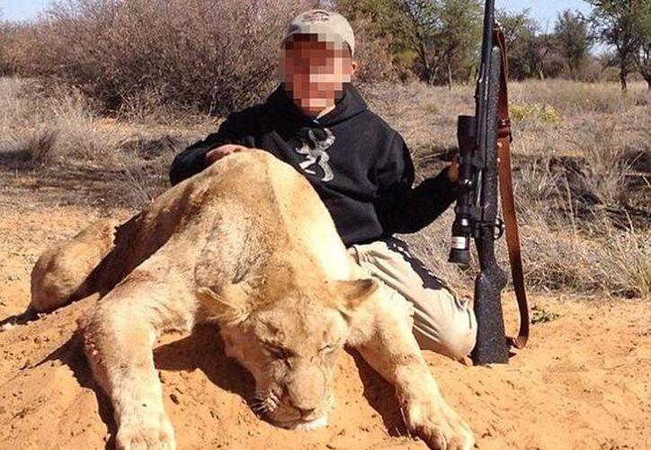 El cazador Allen Tarpley colgó en Internet una polémica fotografía de su hijo de siete años que sujeta un rifle y un león muerto. (@louisa1000)