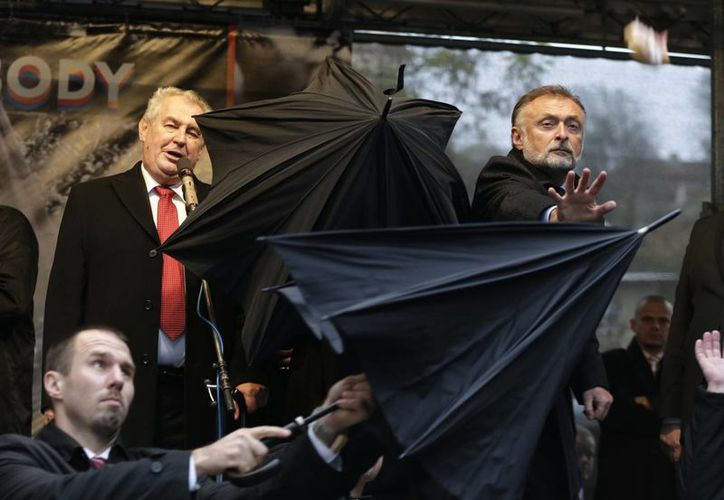 Guardias de seguridad utilizaron paraguas para proteger al presidente checo Milos Zeman (arriba a la izquierda), durante su discurso por el 25 aniversario del final del comunismo en la República Checa. (Agencias)