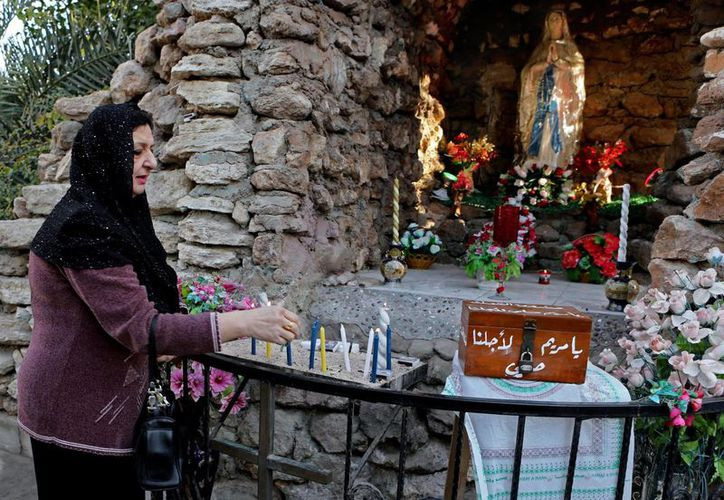 Una cristiana enciende velas antes de una misa por la Navidad en la iglesia de la Madre Teresa en Basora, la segunda ciudad más grande de Irak. (Agencias)