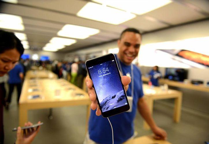 Un empleado de Apple Store muestra un nuevo iPhone en el Eaton Centre Apple Store. (Agencias)