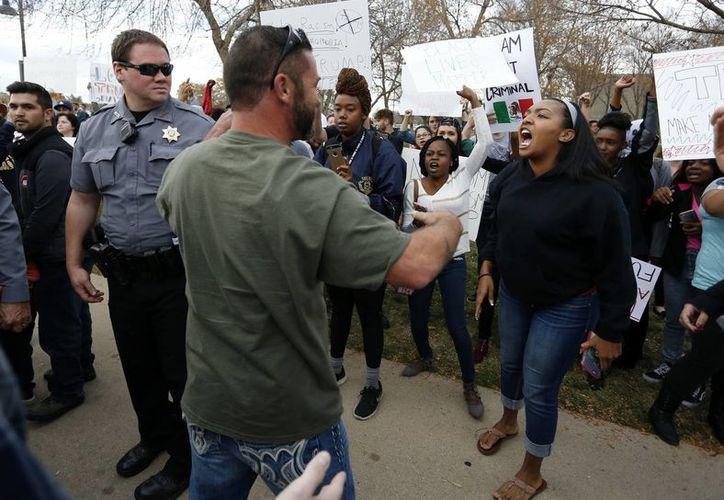 Una manifestante en contra del candidato presidencial republicano Donald Trump (d), y un simpatizante de a Trump se enfrentan verbalmente luego de que el empresario acudió a un acto proselitista en la Universidad Northern Colorado. (AP/Brennan Linsley)
