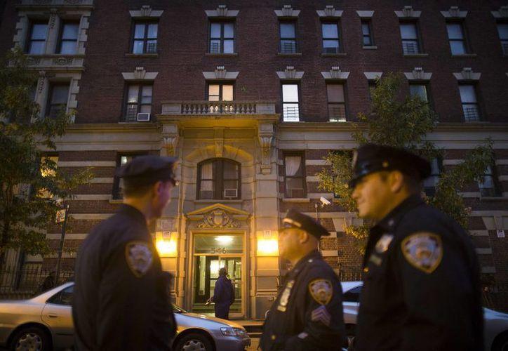 Policías de Nueva York vigilan el edificio donde vivía Craig Spencer, un doctor que hace poco regresó a la ciudad después tratado en el Oeste de África a pacientes con ébola, virus del cual aparentemente se contagió. (Foto: AP)
