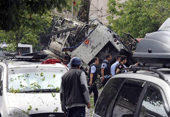Funcionarios de seguridad turcos y bomberos trabajan en la zona donde explotó un coche bomba al paso de un autobús que trasladaba a agentes antimotines, en Estambul. (Agencias)