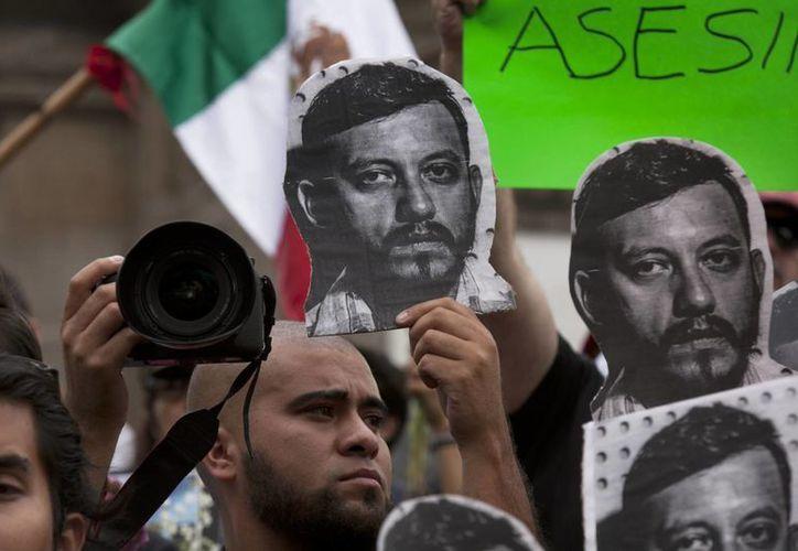 Cientos de personas se congregaron en el Ángel de la Independencia para condenar la muerte del fotógrafo Rubén Espinosa. (AP)