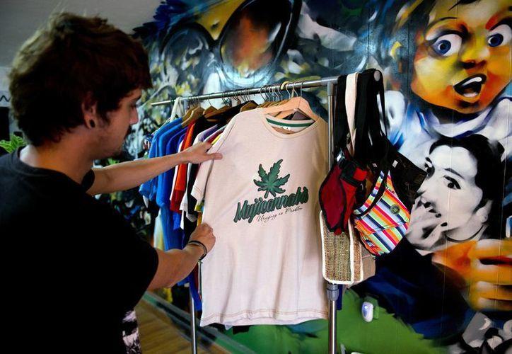 """Un cliente observa una camiseta decorada con una hoja de marihuana y la palabra """"Mujicannabis"""" en una tienda de Montevideo, Uruguay. (Agencias)"""