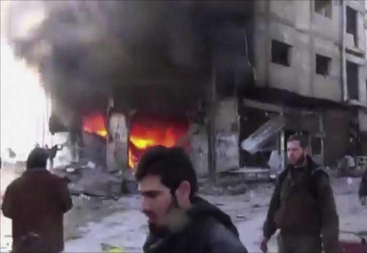 En esta imagen hecha de vídeo obtenido de la Red de Noticias Shaam. se ve a la gente que camina al lado de un edificio en llamas en su búsqueda de sobrevivientes. (Agencias)