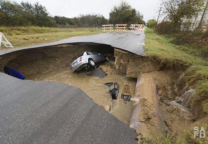 Un hueco profundo que se abrió el domingo 4 en un camino en San Antonio, Texas. Una subjefa de policía fuera de servicio murió y dos personas más resultaron heridas debido al accidente. (Departamento de Bomberos de San Antonio vía AP)