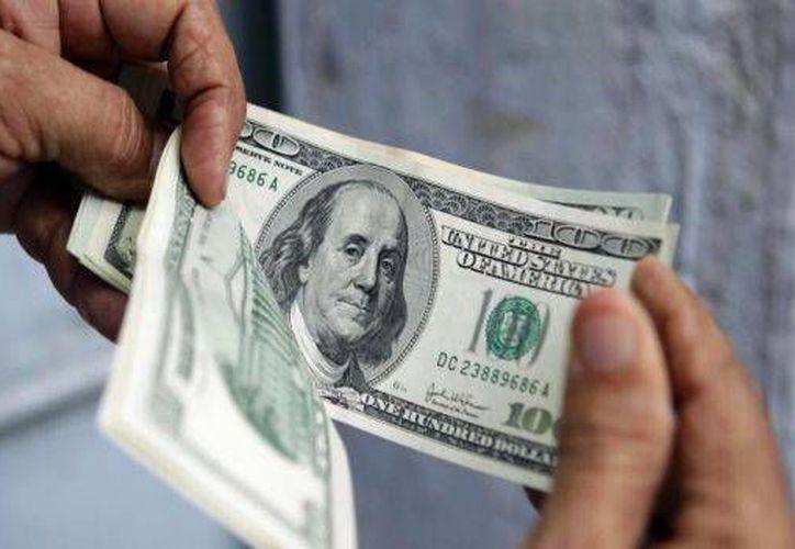 En las casas de cambio del AICM el dólar estadounidense se ofrece en 20.67 pesos en promedio. (Archivo/AP)