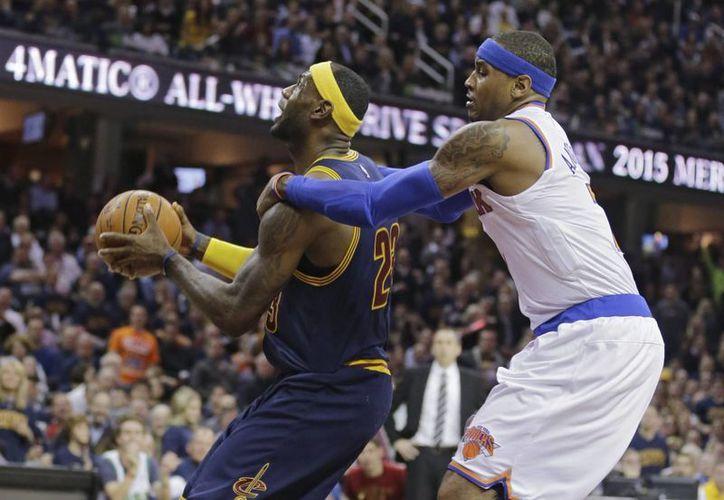 LeBron James (azul) y Carmelo Anthony disputan un balón en el partido entre Cavaliers y Knicks, en los albores de la nueva temporada de la NBA. (Foto: AP)
