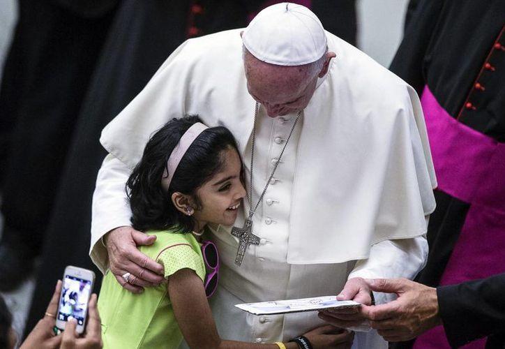 Papa Francisco saluda a una joven participante en su audiencia general semanal en el Aula Pablo VI, en Ciudad del Vaticano. (EFE)