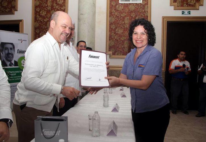 Gilda Flota Rosado, gerente de Recursos Humanos de Milenio Novedades, recibió el reconocimiento para la empresa de manos de Miguel Antonio Morales Cervera, director en Yucatán y Campeche de Fonacot. (José Acosta/SIPSE)