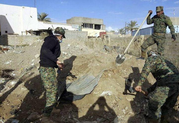 Las fuerzas de seguridad iraquíes trabajan en el sitio donde se encontró una osa común, se cree que contiene los cuerpos de civiles iraquíes asesinados por militantes del grupo Estado Islámico en Ramadi. (Foto AP)