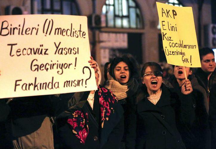 Varias mujeres manifiestan con pancartas en las que se puede leer 'AKP (el partido gobernante), quédate lejos de las niñas' en Estambul, Turquía, tras la aprobación de una polémica legislación sobre abusos sexuales contra mujeres. (EFE)