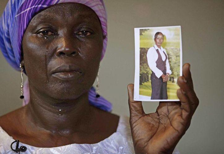 Una mujer muestra la foto de su hija, quien fue secuestrada por el grupo de la Boko Haram. (Agencias)