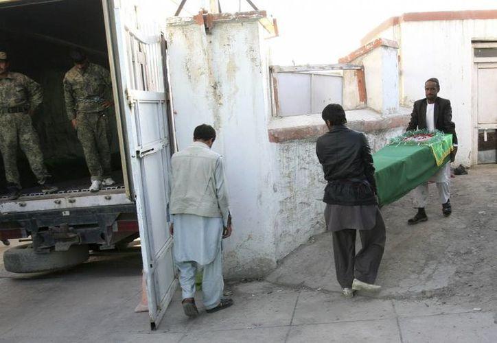 Oficiales de seguridad portan el ataúd de uno de los policías afganos muertos en un atentado en una carretera de en el sureste de Afganistán. (EFE)
