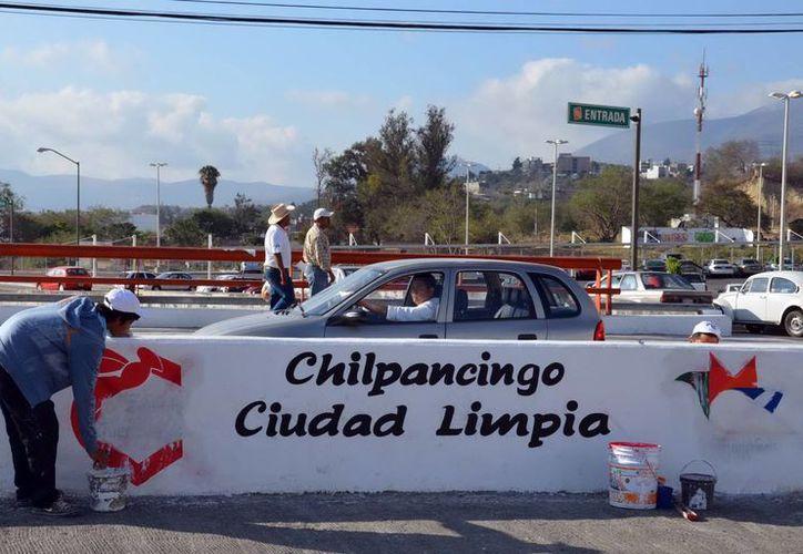 Empleados del Ayuntamiento de Chilpancingo borran las consignas escritas durante la marcha de ayer de maestros. (Notimex)