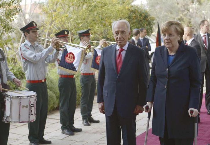 El presidente israelí, Simón Peres (centro), y la canciller alemana Angela Merkel (der), pasan revista a una guardia de honor durante su encuentro en la residencia presidencial, en Jerusalén, Israel. (EFE)