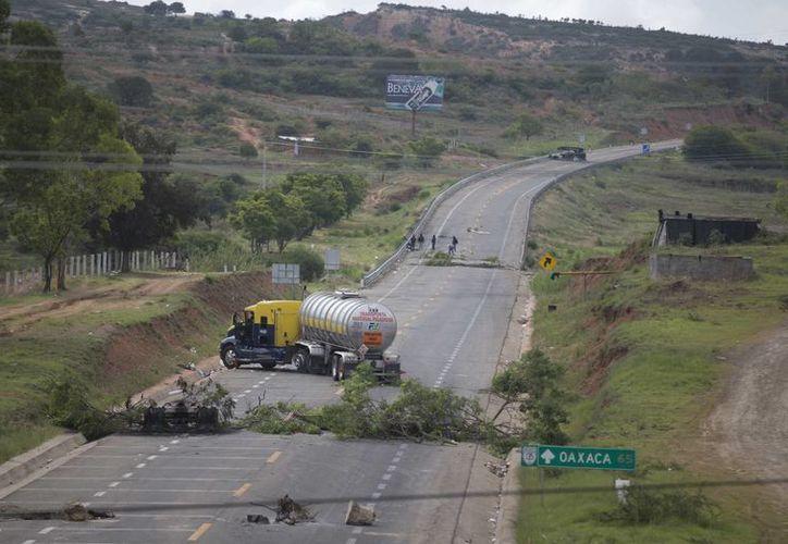 Las carreteras bloqueadas en Oaxaca ya comienzan a tener consecuencias para los empresarios yucatecos de los sectores industrial y del comercio. (Archivo AP)
