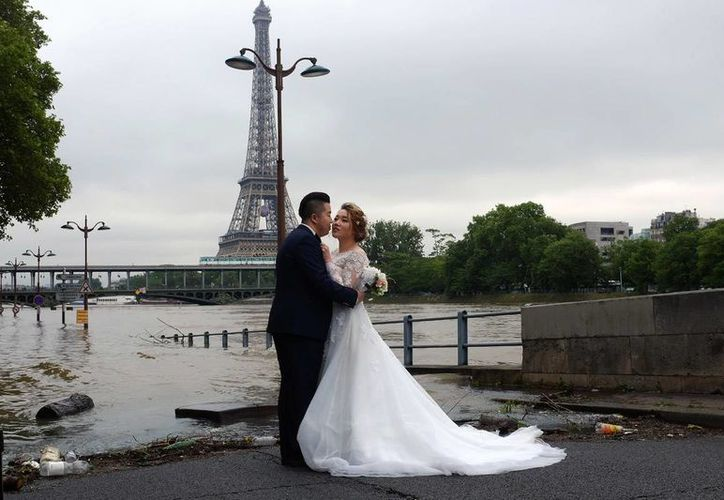 Una pareja de recién casados durante su sesión de fotos con el río Sena de fondo, en las inundadas calles de Paris. (AP)